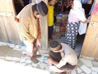 Anggota Polsek Mattiro Sompe, bripka Safiuddin memasangkan sendal kepada pria diduga gangguan jiwa.(ist)