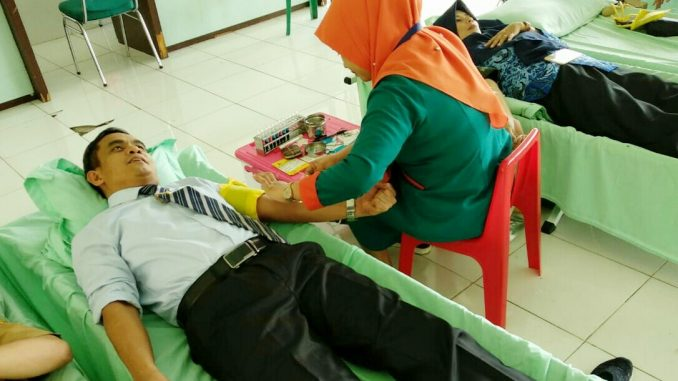 Sekda Sidrap, Sudirman Bungi sedang melakukan donor darah di HUT Korpri