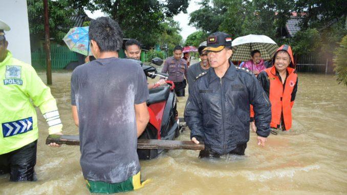 Kapolres Barru AKBP Burhaman membantu evakuasi satu unit sepeda motor di tengah luapan banjir.