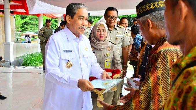 Bupati Sidrap H Dollah Mando menyerahkan sertifikat tanah kepada warga.