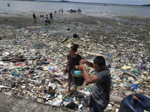 Warga mengambil minyak yang tumpah di laut.