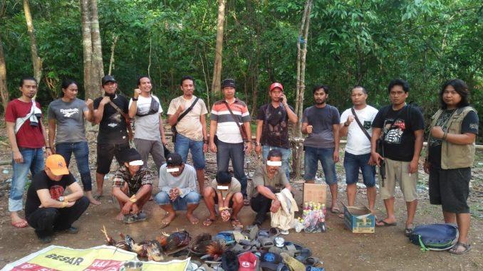 Personel Polres Pinrang berfoto usai berhasil menggrebek arena judi sabung ayam di pegunungan.